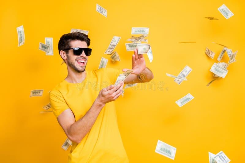 Foto di un giovane affascinante e imprudente tizio che butta via banconote in denaro da ricchi che indossa una maglietta sporca d immagini stock libere da diritti