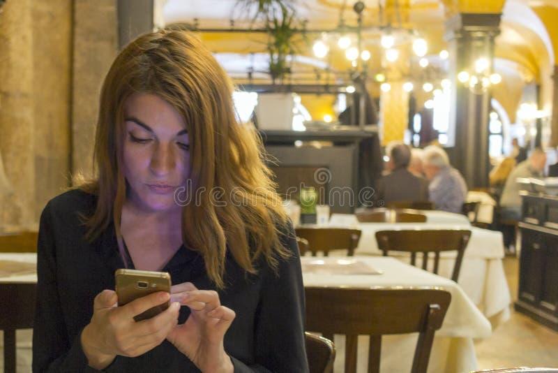 Foto di un messaggio castana della lettura di signora su un telefono cellulare, vestita in una blusa nera, sedentesi in un caffè immagine stock libera da diritti
