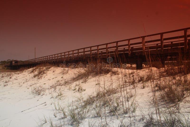 Foto di un pilastro che si sporge sopra la spiaggia sabbiosa immagini stock libere da diritti