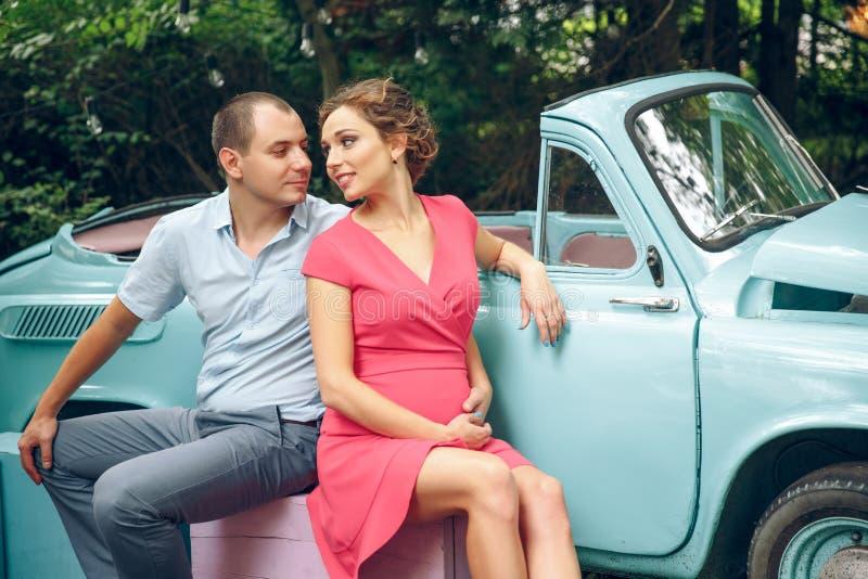 Foto di una coppia incinta Retro automobile blu nei precedenti immagine stock
