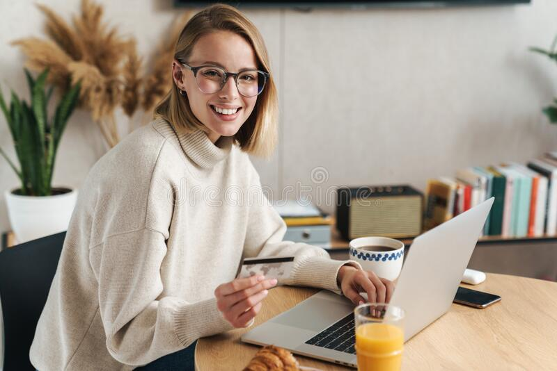 Foto di una donna bionda allegra che tiene in mano una carta di credito e usa un portatile immagine stock libera da diritti