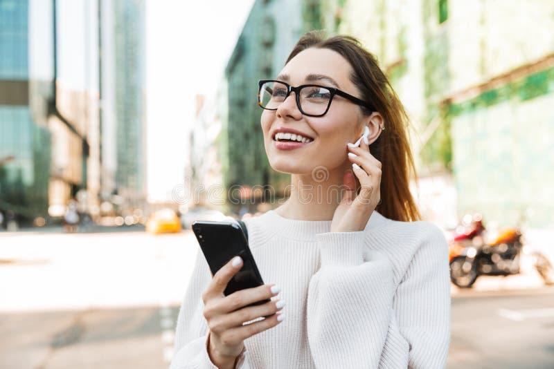 Foto di una donna felice sorridente che usa il cellulare e l'auricolare mentre cammina per strada nella grande città immagine stock libera da diritti