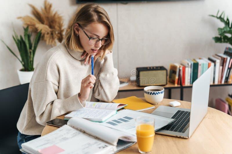Foto di una donna molto attraente che esamina i documenti e usa il computer portatile immagine stock