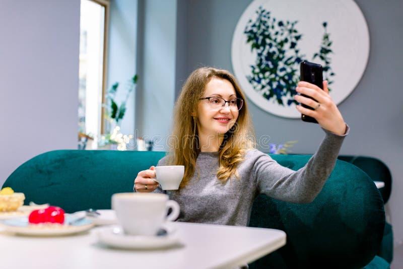 Foto di una giovane donna carina seduta al bar a fare il selfie con una tazza di caffè Guarda il telefono immagini stock