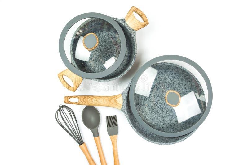 Foto di una padella ceramica con un coperchio e le pentole con un coperchio isolato su un fondo bianco fotografia stock libera da diritti