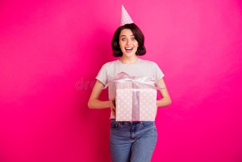 Foto di una ragazza allegra e carina con le mani in mano una scatola giftbox con cappello, jeans jeans denim fotografia stock