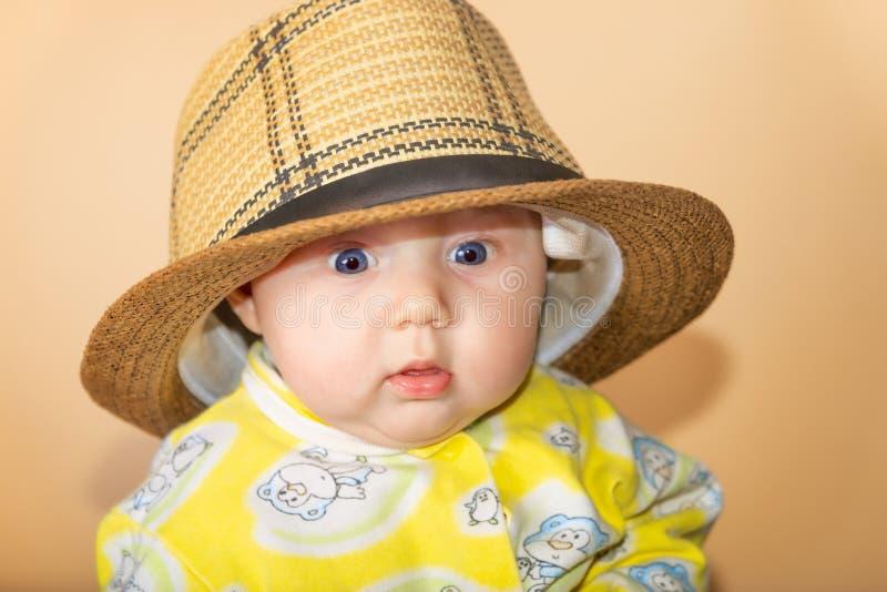Foto di una ragazza nello studio, ritratto di un neonato in un cappello di paglia fotografia stock