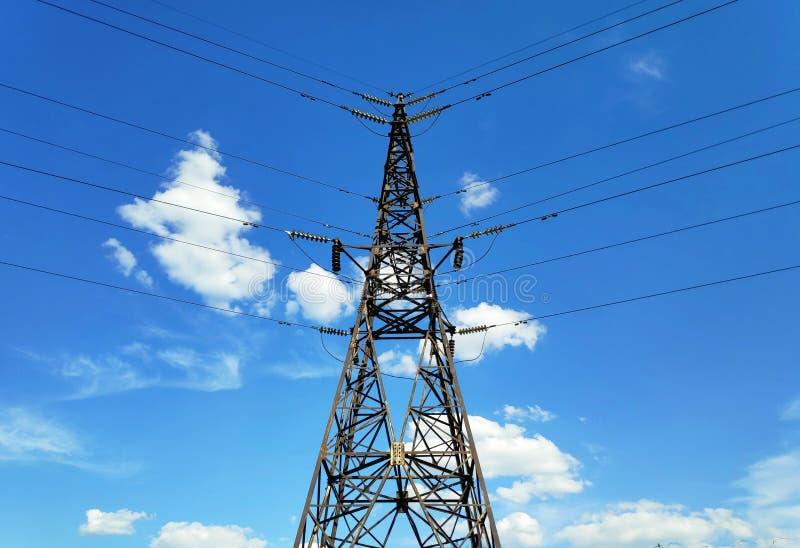 Foto di una torre del trasporto di energia del metallo con i cavi su un fondo di cielo blu luminoso con le nuvole bianche fotografie stock libere da diritti