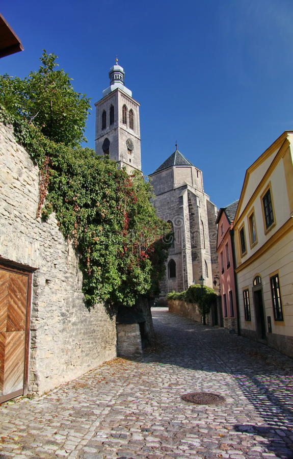Foto di vecchie vie strette del ciottolo (pietra naturale) della cittadina europea medievale, andanti ad una chiesa cattolica ant fotografie stock