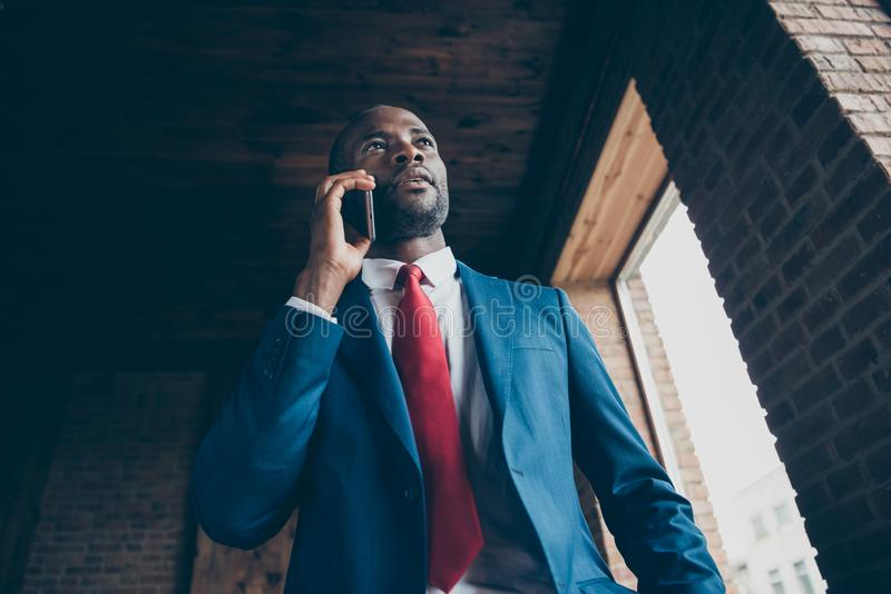 Foto di vista di angolo basso della mano scura del telefono della tenuta del tipo della pelle che parla del costume elegante di u immagine stock