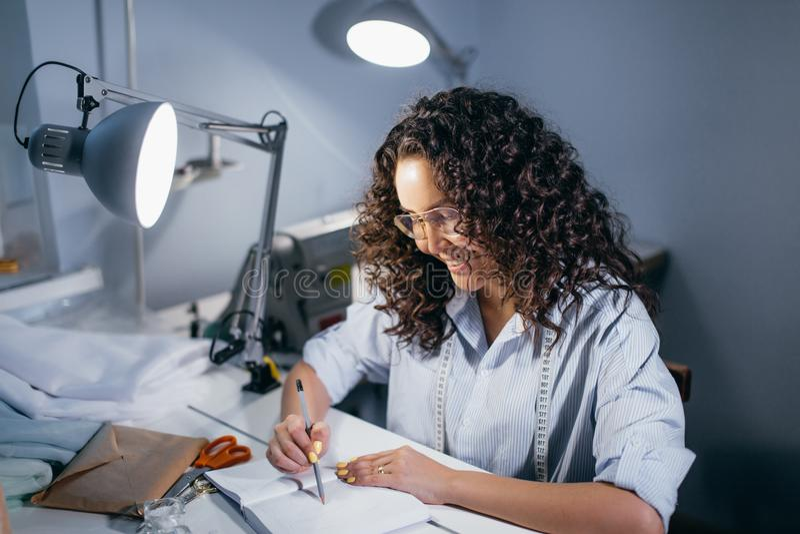 Foto di vista laterale del sarto da donna femminile che si china la tavola fotografia stock libera da diritti