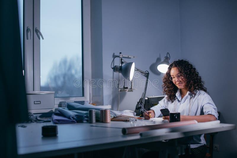 Foto di vista laterale della donna che si siede alla finestra con l'aggeggio in studio fotografia stock