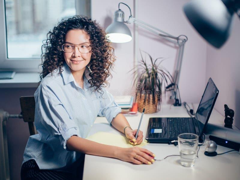 Foto di vista laterale della ragazza piacevole che fa reseach sul computer portatile immagini stock libere da diritti