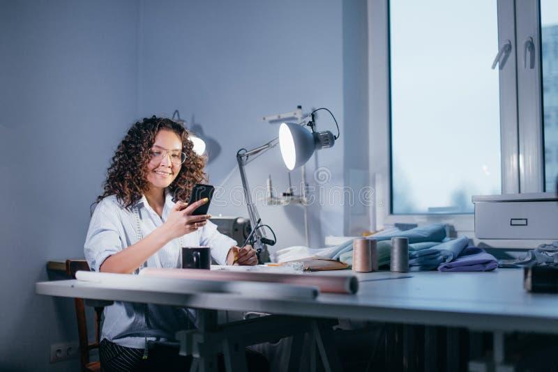 Foto di vista laterale della ragazza sorridente che fa telefonata all'atelier fotografia stock