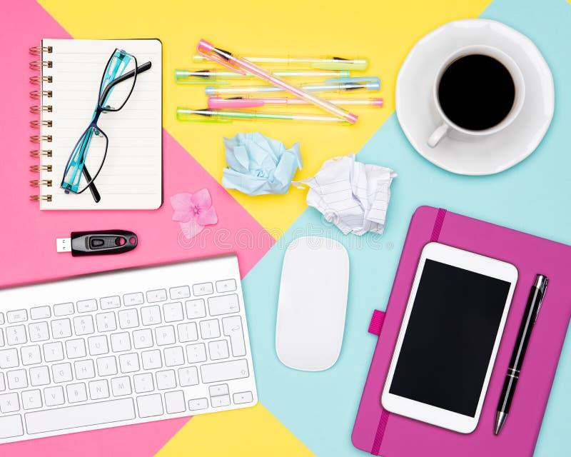 Foto di vista superiore di area di lavoro con la tazza della tastiera, del blocco note e di caffè su fondo pastello Concetto di l immagini stock