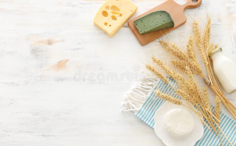 Foto di vista superiore dei prodotti lattier-caseario sopra fondo di legno bianco Simboli della festa ebrea - Shavuot fotografie stock libere da diritti
