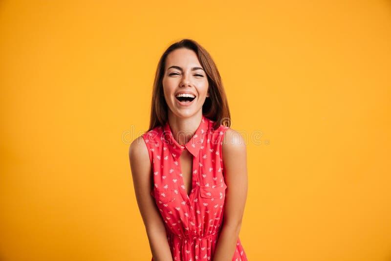 Foto die van jonge vrij donkerbruine vrouw in rode kleding lachen stock afbeelding
