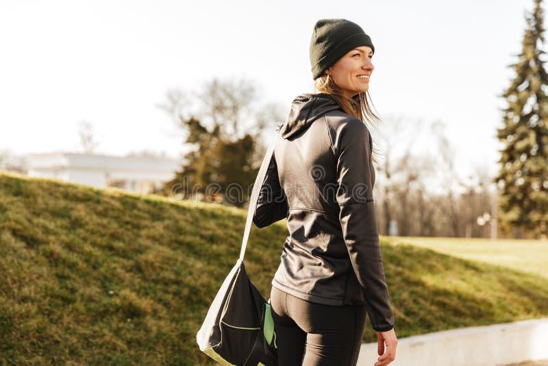 Foto die van joyous atletisch meisje in zwarte sportkleding, lopen met royalty-vrije stock foto