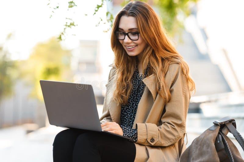 Foto die van joyous vrouw aan laptop werken terwijl het zitten op bank in stadsstraat stock afbeeldingen