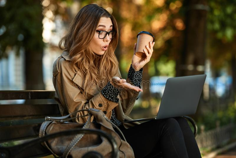Foto die van joyous vrouw aan laptop werken terwijl het zitten op bank in zonovergoten steeg stock fotografie