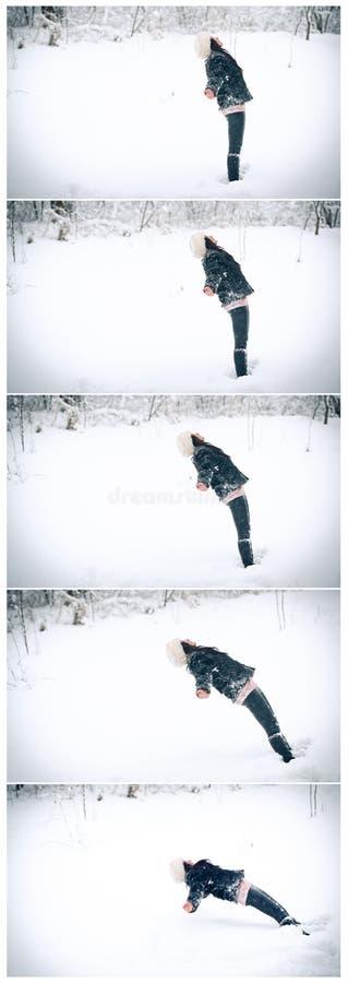 Foto dinamica della giovane donna che cade giù su lei indietro sulla neve Ragazza nel gioco nero nel paesaggio di inverno fotografia stock