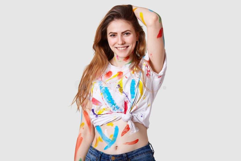 A foto do artista fêmea deleitado feliz trabalha no ptoject da arte, sorrisos positivamente, sente inspirada e contente, tem a pa foto de stock royalty free