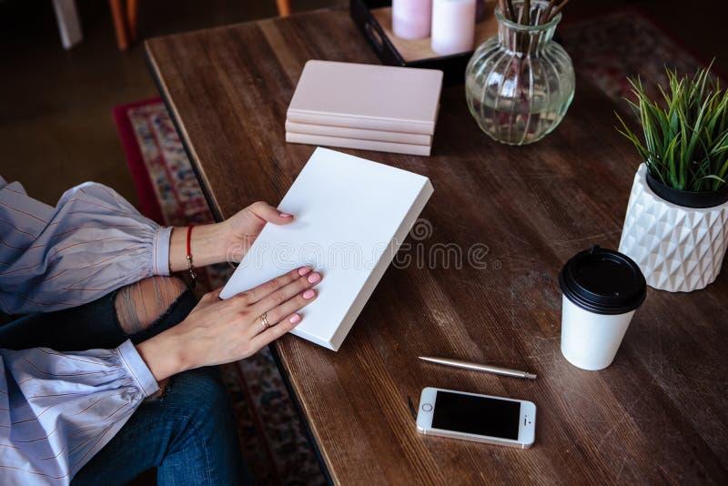 Foto do close-up do caderno do planificador em uma tabela de madeira A mão fêmea escreve no papel imagens de stock