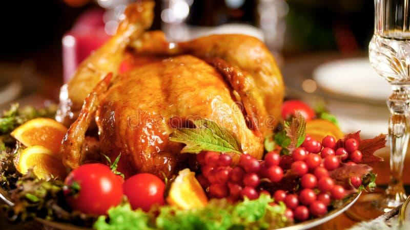 Foto do close up da galinha roasted no prato grande na tabela de jantar do Natal fotos de stock royalty free