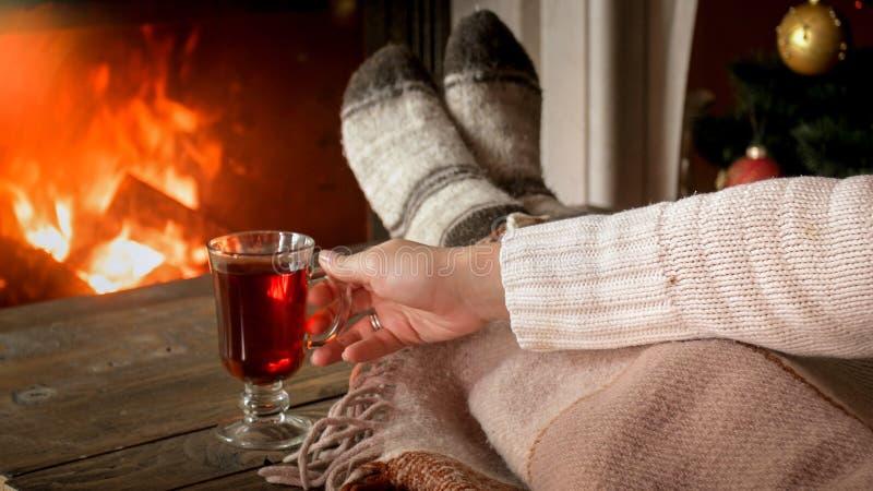 Foto do close up da jovem mulher que aquece-se com chá quente na sala de visitas com chaminé ardente fotografia de stock royalty free