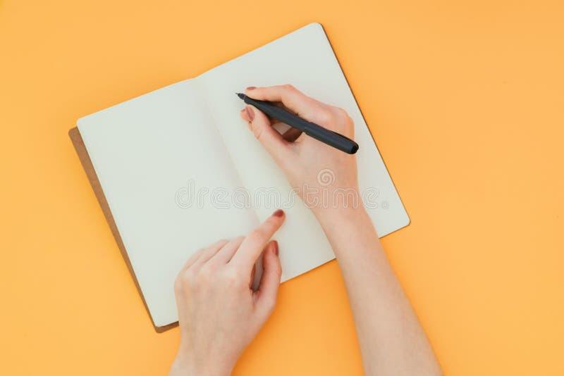A foto do close up da mão de uma mulher com uma pena, escreve em um caderno limpo em um fundo alaranjado imagens de stock