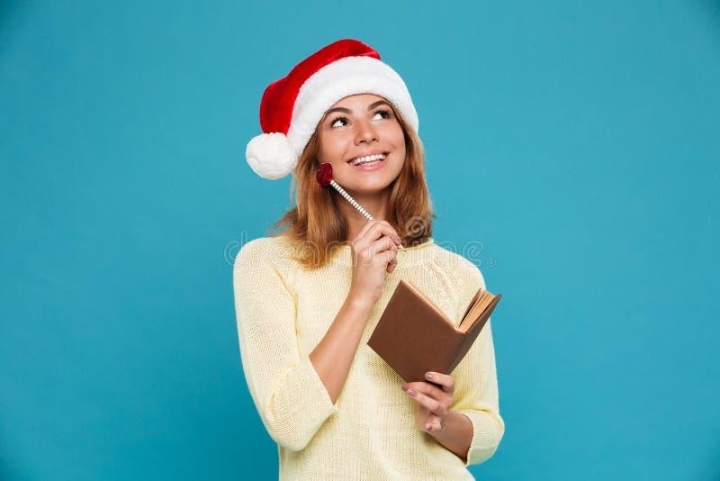 Foto do close-up da menina moreno de pensamento bonita no chapéu do ` s de Santa que guarda o lápis e o bloco de notas, olhando d imagem de stock