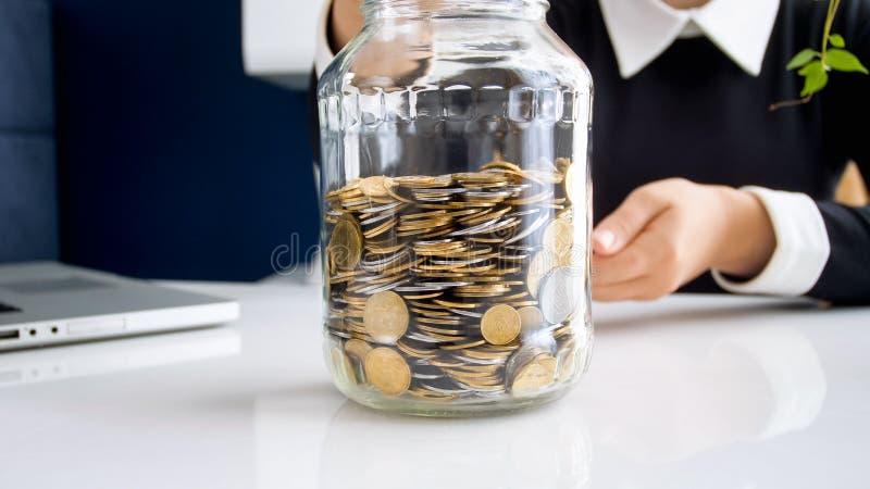 Foto do close up da mulher de negócios nova que põe moedas no frasco de vidro imagens de stock