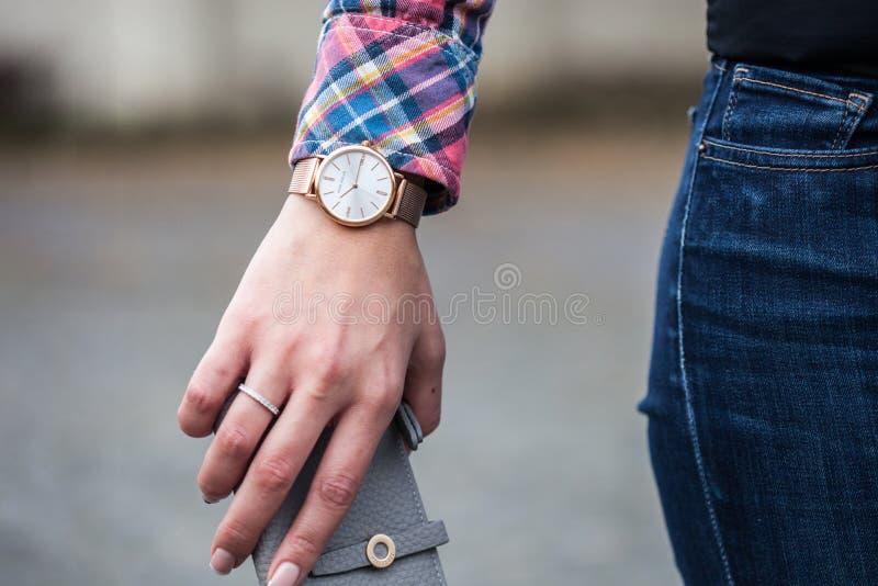 Foto do close up da pessoa que veste em volta do relógio análogo quadro Ouro-colorido fotos de stock royalty free