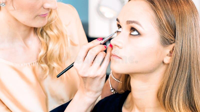A foto do close up da pintura profissional do maquilhador modela os olhos com escova imagens de stock