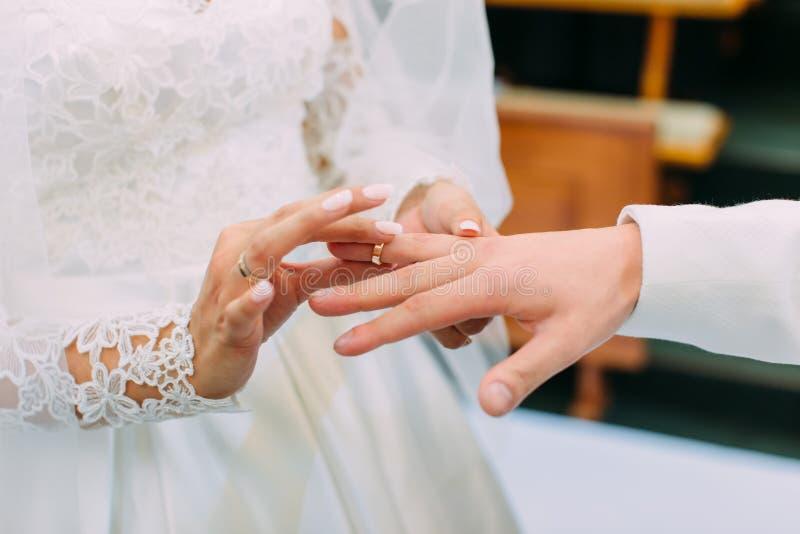 Foto do close-up das mãos da noiva que põe a aliança de casamento sobre o dedo do noivo fotografia de stock royalty free