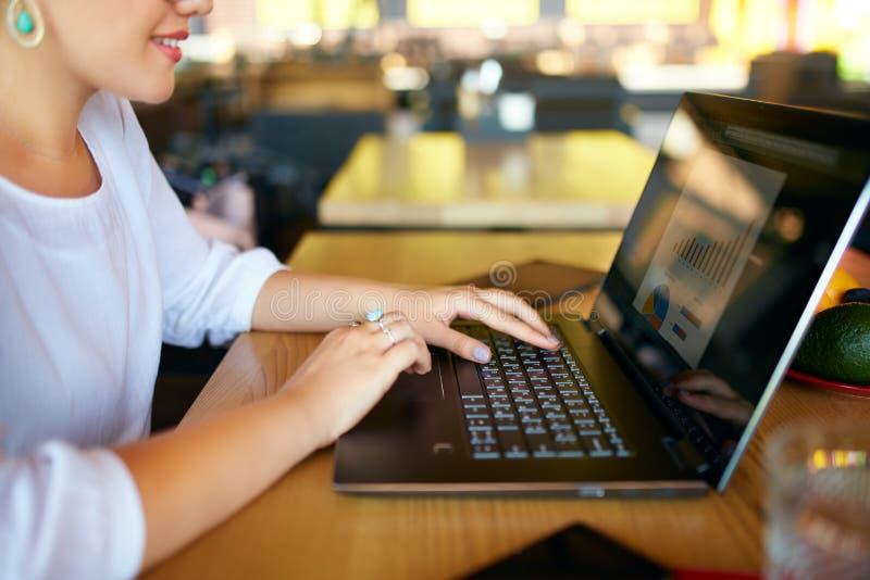 Foto do close-up das mãos fêmeas que datilografam no teclado do portátil e que usam o touchpad Diagrama e cartas na tela Negócios foto de stock royalty free