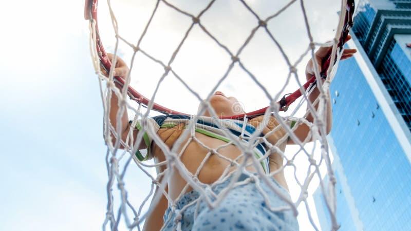 Foto do close up de 3 anos ativos do menino idoso da criança que guarda no anel da rede do basquetebol Conceito de crianças ativa foto de stock