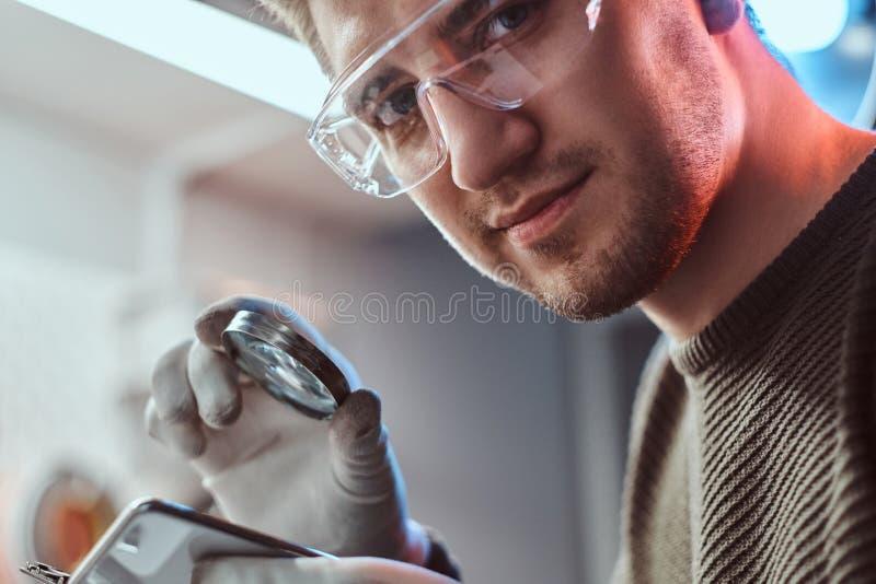 Foto do close up de um técnico eletrônico nos óculos de proteção que guardam a lupa e os olhares na câmera foto de stock royalty free