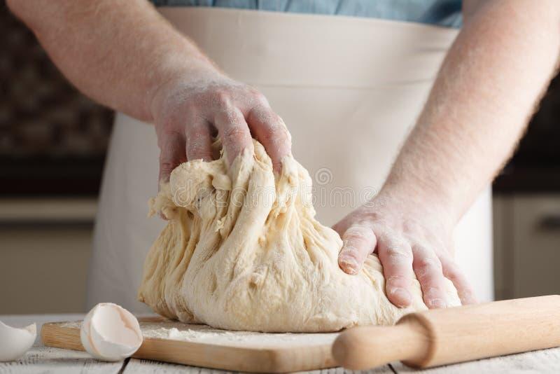 Foto do close up do padeiro que faz a massa de fermento para o pão fotografia de stock