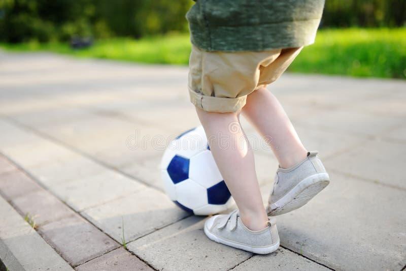 Foto do close-up do rapaz pequeno que tem o divertimento que joga um jogo de futebol no dia de verão ensolarado fotos de stock royalty free