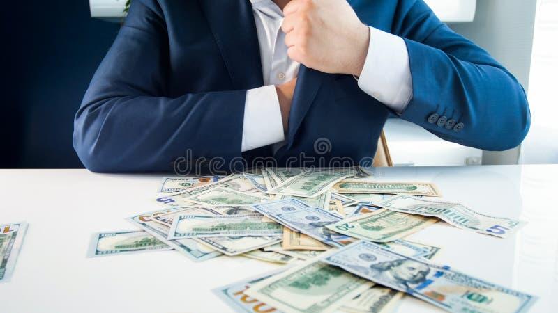 Foto do close up do homem de negócios ávido que enche seus bolsos com o dinheiro foto de stock