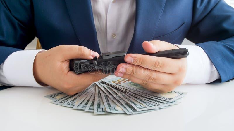 Foto do close up do homem de negócios no terno com lotes do revólver da terra arrendada de dinheiro nas mãos imagens de stock