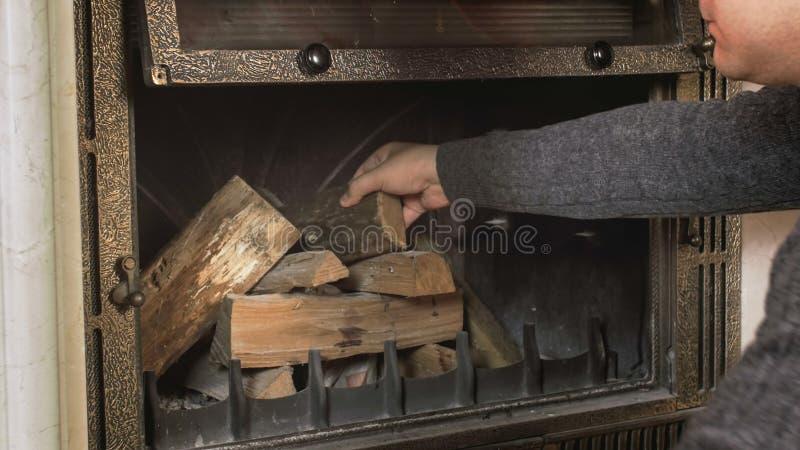 A foto do close up do homem que põe de madeira entra a chaminé na sala de visitas imagens de stock royalty free