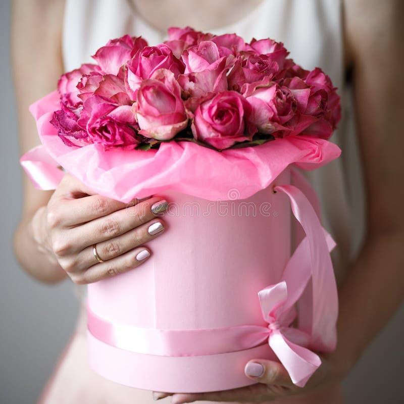 Foto do close-up do ramalhete lindo de rosas cor-de-rosa em uma caixa do chapéu Mãos da mulher com manicure imagem de stock royalty free