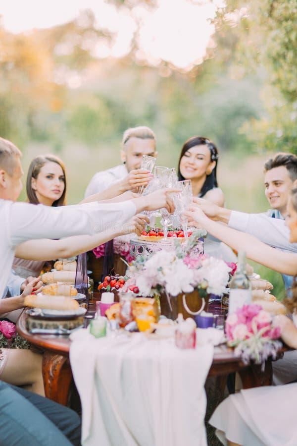 A foto do close-up do tinido dos recém-casados e dos convidados seus vidros e assento na tabela completamente do alimento delicio imagem de stock