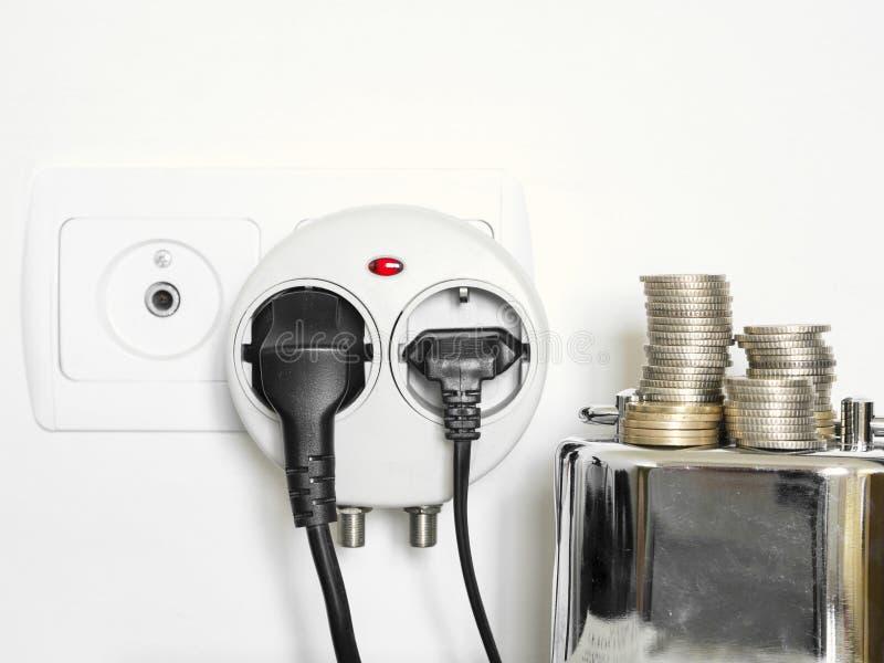 A foto do conceito com mealheiro e as moedas que mostram a tomada e o consumo de eletricidade obstruíram dentro a tomada de pared imagens de stock