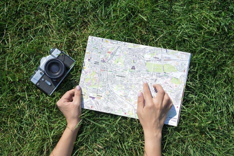Foto do conceito do curso com o mapa da cidade europeia velha e o dedo e a câmera velha da mulher imagem de stock