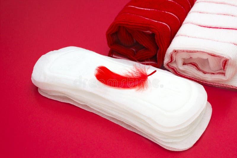 Foto do conceito da higiene Toalhas de terry do banho, pena vermelha no montão de almofadas menstruais da mulher para o período d foto de stock royalty free