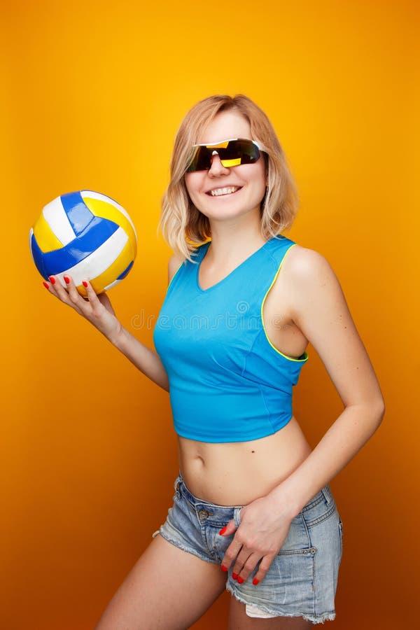 Foto do desportista novo nos óculos de sol com voleibol no fundo alaranjado imagens de stock