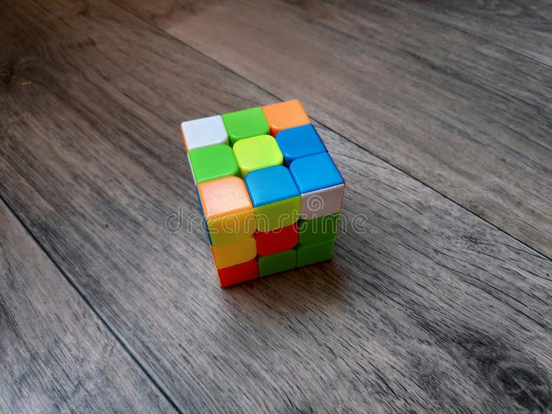 Foto do enigma do cubo de um Rubik em um fim unassembled do formulário acima em uma superfície de madeira foto de stock